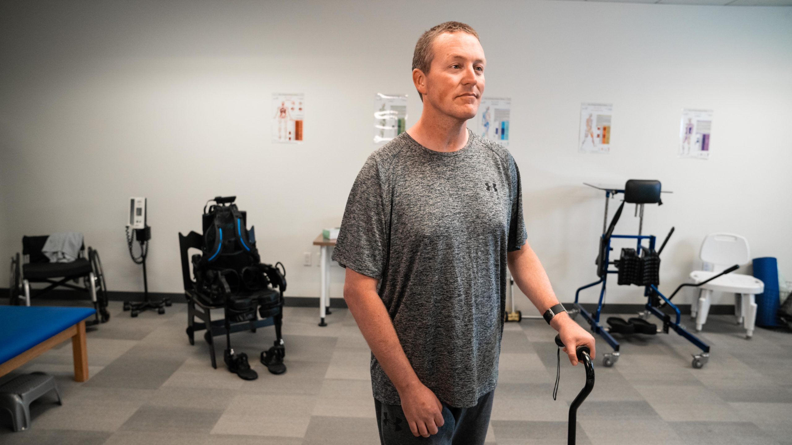 Man standing with a walking cane, in the background there is an Ekso Bionics exoskeleton suit sitting in a wheelchair.
