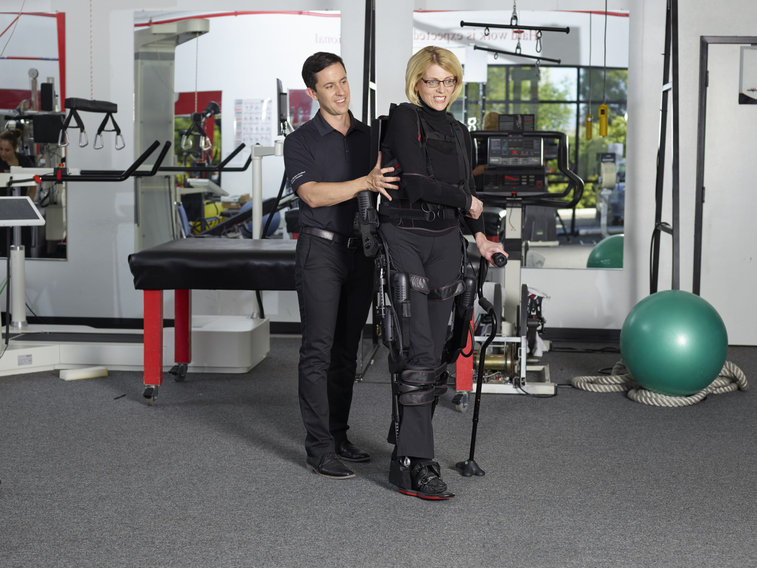 Image of woman taking Ekso Bionics assisted steps with the help of a physical therapist.