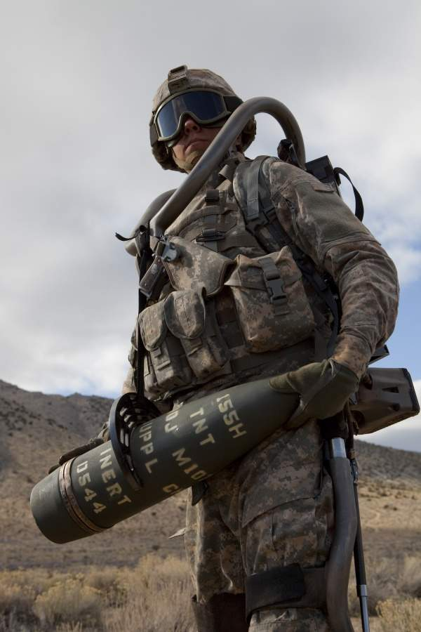 US Navy man carrying heavy equipment while wearing an Ekso Bionics EksoVest, which increases his carrying capabilities.