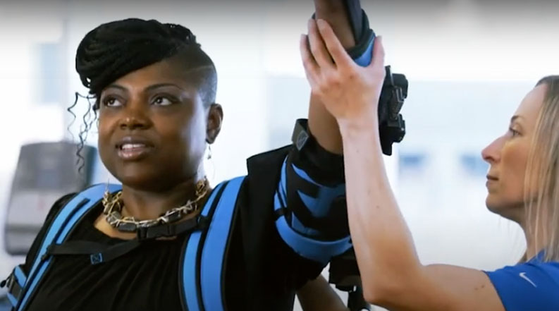Woman wearing Ekso Bionics EksoUE lifting her left arm in the air with the assistance of a pysical therapist.